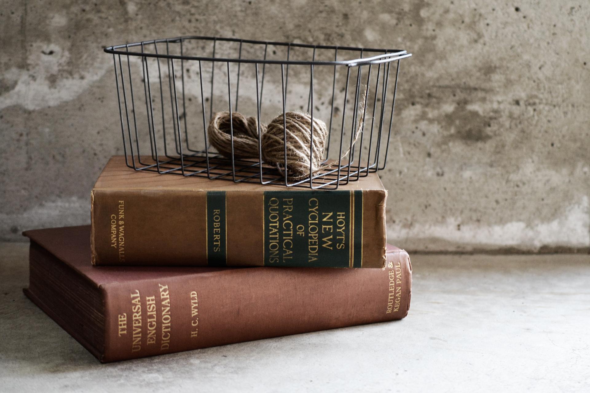 本の上にワイヤーバスケットを置いたディスプレイ